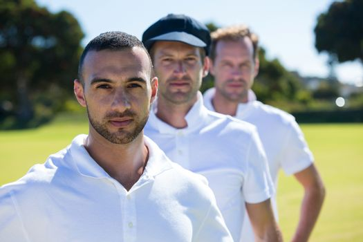 Portrait of cricket players standing at grassy field