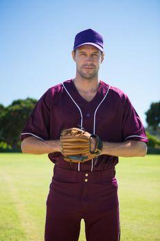 Portrait of confident baseball pitcher standing against sky