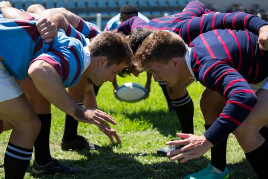 Close up of men playing rugby at grassy field
