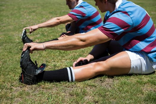 Rugby players stretching while sitting on grassy field