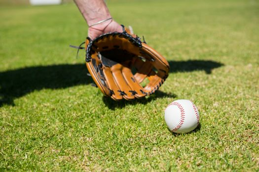 Hand of baseball pitcher by ball on field