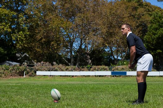 Rugby player playing on grassy field against trees