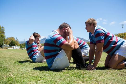 Close up of rugby players exercising on grassy field