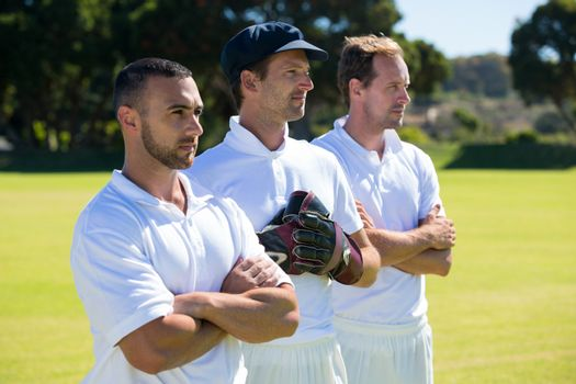 Confident cricket players standing at grassy field