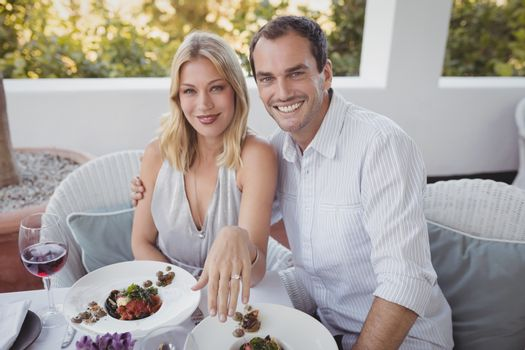 Portrait of romantic couple with their engagement ring