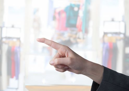 Hand pointing in  air of  clothes retail store