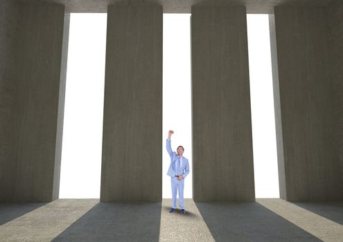 Successful businessman standing against columns
