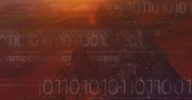 White binary code against mountain rock in sunset