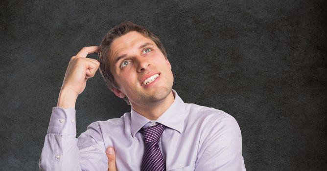 Confused businessman scratching head against blackboard