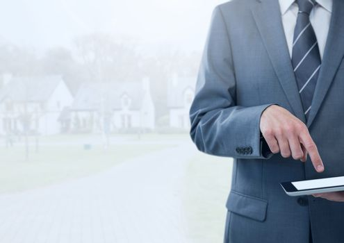 Businessman holding tablet in bright housing estate