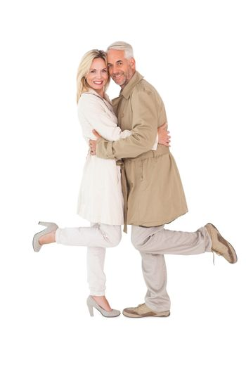Happy couple posing in trench coats