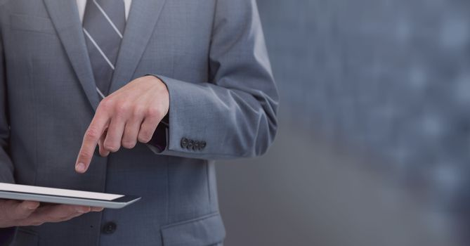 Businessman holding tablet with mid tone background