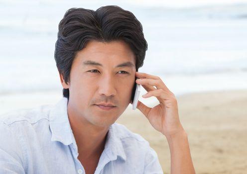 Man on phone against blurry beach