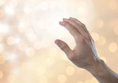 Hand touching brightness with sparkling light bokeh background