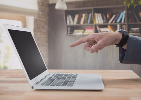 Businessman pointing at laptop with bookshelf