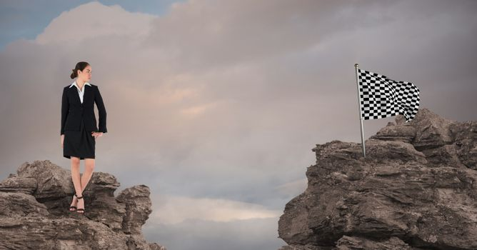 Businesswoman and checked flag over rocks