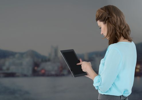 Businesswoman holding tablet with distant grey city background