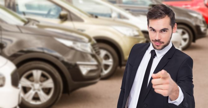 Businessman pointing against car in showroom