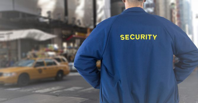 Back of security guard against blurry street