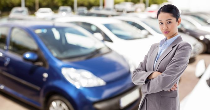 Businesswoman with arms crossed in car showroom