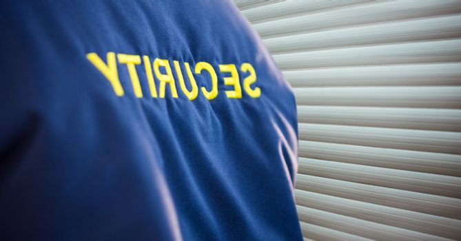 foreground of the security guard jacket,  near the blind