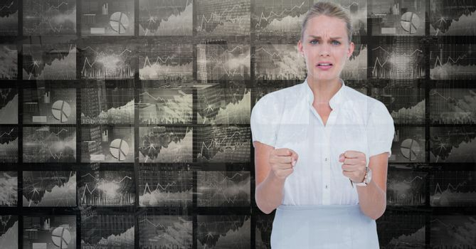Woman showing fists against graphs