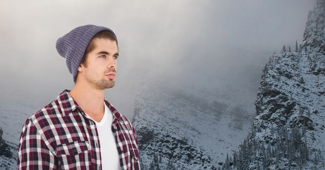 Young hipster wearing knit hat against snowcapped mountains