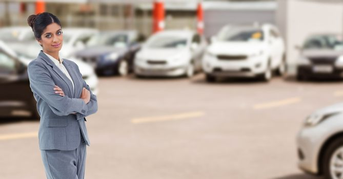 Portrait of businesswoman with arms crossed in car showroom