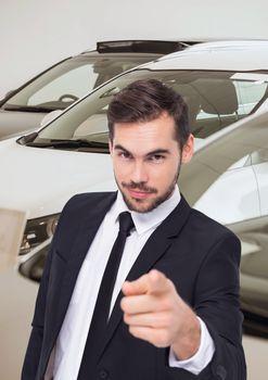 Salesman pointing against cars in showroom