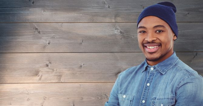 Hipster wearing knit hat against wooden wall