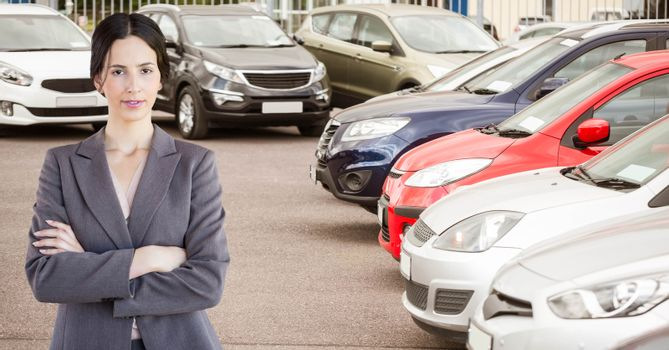 Confident businesswoman standing arms crossed in car showroom