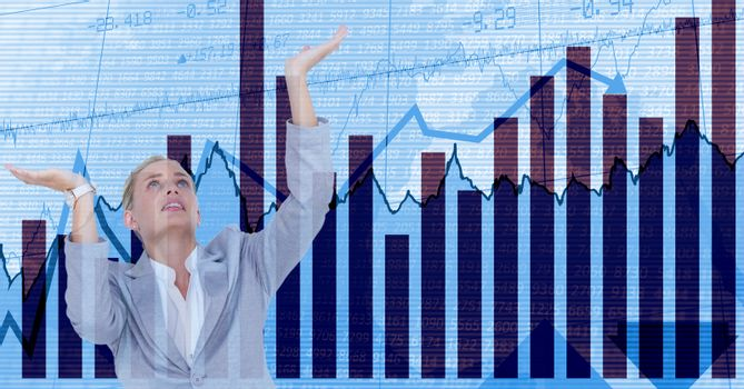 Businesswoman with arms raised against graphs