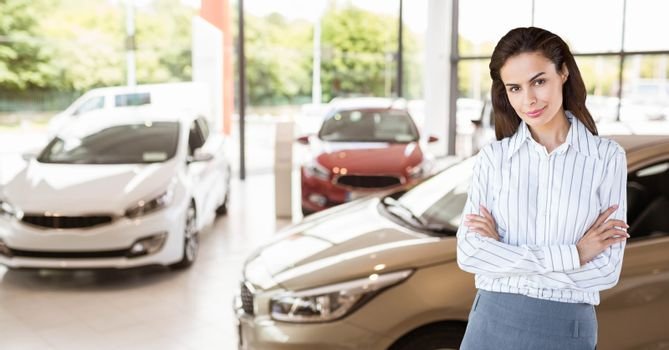 Businesswoman with arms crossed ion car showroom
