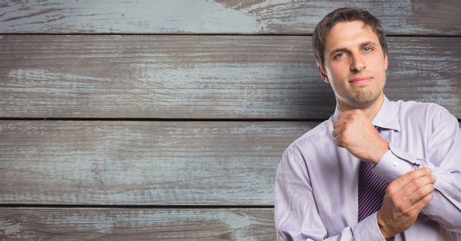 Portrait of confident businessman buttoning sleeve against wooden wall