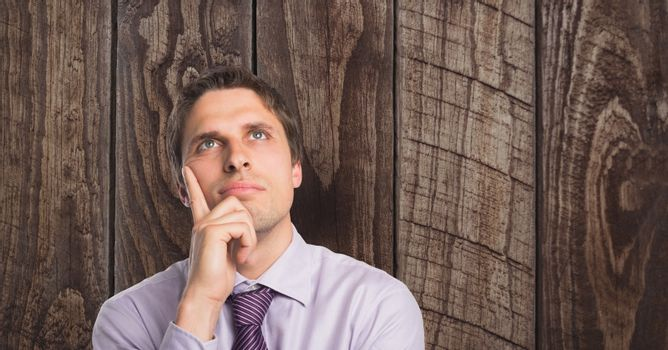 Thoughtful businessman with hands on chin against wooden wall