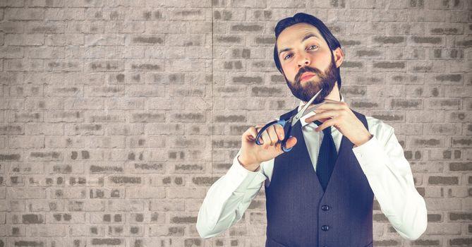 Hipster cutting beard against wall