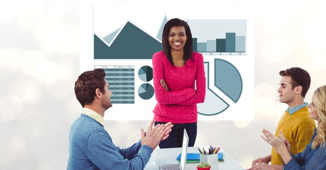 Colleagues applauding for businesswoman against graphs