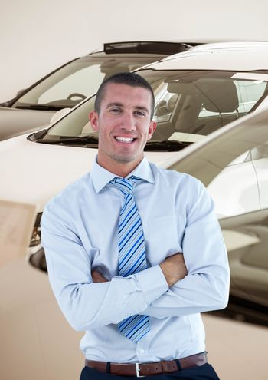 Smiling businessman standing arms crossed in car showroom