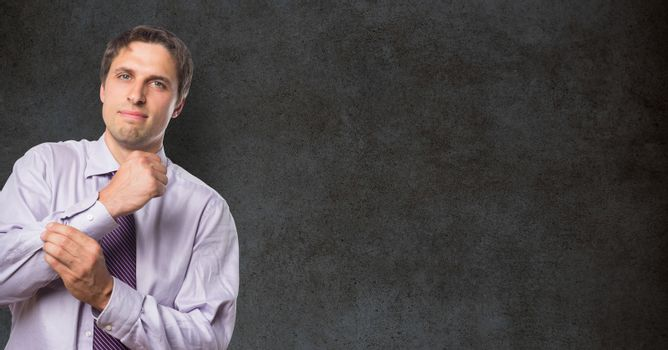 Portrait of confident businessman buttoning sleeve against blackboard