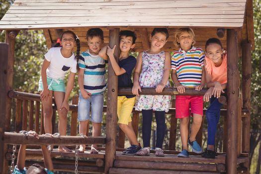 Portrait of schoolkids standing in wooden shelter