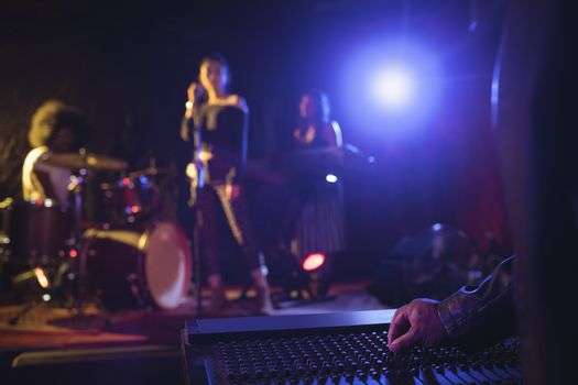 Musicians operating sound mixer with performers on illuminated stage in nightclub
