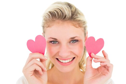 Attractive young blonde holding little hearts on white background