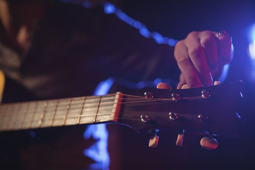 Mid section of musician adjusting tuning peg