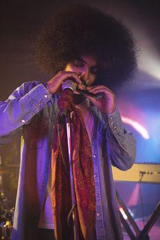 Male musician playing mouth organ in illuminated nightclub