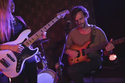 Musician playing guitar in nightclub