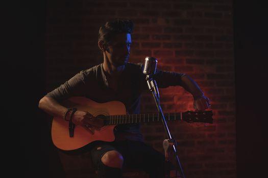 Male singer adjusting tuning pegs of guitar in nightclub