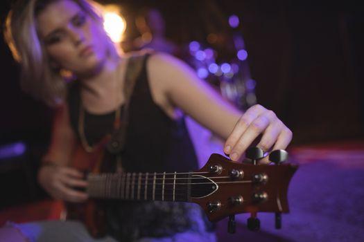 Singer adjusting tuning peg of guitar in nightclub