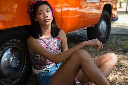 Woman relaxing against camper van in the park