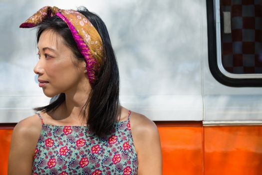 Woman leaning on camper van in the park