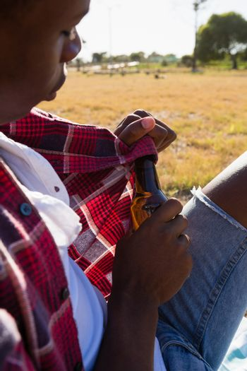 Man opening the lid of beer bottle in the park